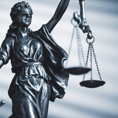 Blindfolded figure of Justice holding scales and a sword conceptual of the courts, judgement, law and order in a beam of light over a grey background with copy space